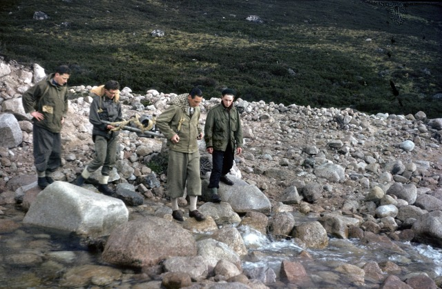Malcolm Douglas and students carrying a rock drill to help build bridge at Corrour Bothy, Cairngorms, in 1959